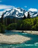 Een rivier stroomt onder a glaciated bergpiek stock foto's
