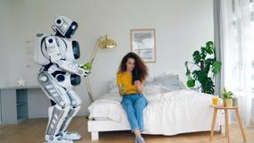 Een robot brengt appelen aan een jonge vrouw stock footage