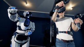 Een robot kopieert mensen` s bewegingen Robotachtig cybernetisch het gokkensysteem van VR stock videobeelden
