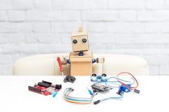 Een robot met handen verzamelt een machine met een zonnebatterij Arti stock foto's