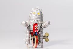 Een robotstuk speelgoed berijdt fiets Royalty-vrije Stock Foto