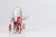 Een robotstuk speelgoed berijdt fiets Stock Afbeelding