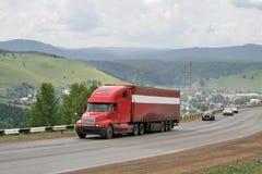 Een rode aanhangwagenvrachtwagen Stock Fotografie