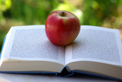Een rode Appel op een Boek Stock Afbeeldingen