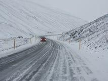 Een rode auto op de winterweg met berg aan de kant van de weg Stock Fotografie