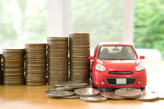 Een rode auto over heel wat gestapelde muntstukken Royalty-vrije Stock Afbeelding