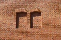 Een rode bakstenen muur, twee bricked-omhooggaande vensters stock foto