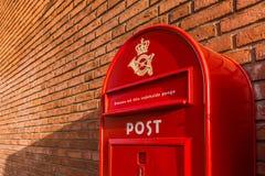 Een rode Deense brievenbus op een bakstenen muur Stock Afbeeldingen
