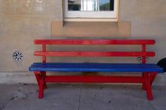 Een rode en blauwe houten bank tegen cementmuur met venster in B royalty-vrije stock foto's