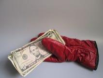 Een rode handschoen houdt geld Royalty-vrije Stock Afbeeldingen