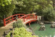 Een rode houten brug over een vijver in een Japanse Gard Stock Foto's