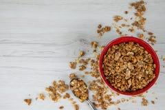 Een rode kom op hoogtepunt van granola met een lepel op witte houten lijst, Stock Foto's