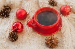 Een rode kop hete koffie, spartakjes, kegels, pijpjes kaneel en Kerstboomdecoratie op een witte bontoppervlakte Stock Afbeelding
