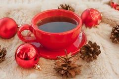 Een rode kop hete koffie, spartakjes, kegels, pijpjes kaneel en Kerstboomdecoratie op een witte bontoppervlakte Stock Fotografie