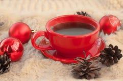 Een rode kop hete koffie, spartakjes, kegels, pijpjes kaneel en Kerstboomdecoratie op een witte bontoppervlakte Stock Foto's