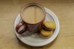 Een rode kop thee en twee koekjes royalty-vrije stock fotografie