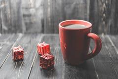 Een rode kop van koffie met rood Kerstmisornament op de donkere houten achtergrond Royalty-vrije Stock Afbeeldingen