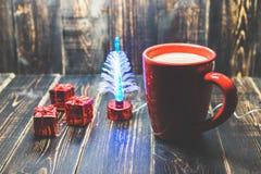 Een rode kop van koffie met rood Kerstmisornament op de donkere houten achtergrond stock afbeelding