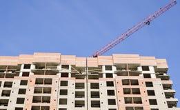 Een rode kraanpijl over een high-rise gebouw Royalty-vrije Stock Fotografie