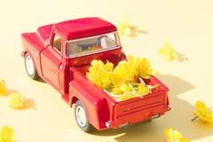 Een rode retro auto met gele bloemen op een roze achtergrond royalty-vrije stock afbeeldingen