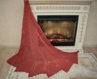 Een rode sjaal wordt uitgespreid op de open haard royalty-vrije stock afbeeldingen
