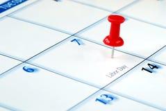Een rode speld die in de kalender wordt genageld Stock Foto