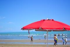 een rode strandparaplu kleurt de stranden van Adriatic Stock Afbeeldingen