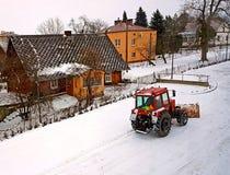 Een rode tractor ontruimt de weg van de sneeuw De winter het schoonmaken van de straat DE COMMUNAUTAIRE DIENST weer Het Dorp van  royalty-vrije stock afbeelding