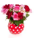 Een rode witte gestippelde vaas met een boeket van rozen Royalty-vrije Stock Afbeelding