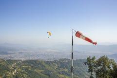 Een rode witte windsock op de achtergrond van een vliegend glijscherm in een duidelijke blauwe hemel en groene bergen met een sta stock fotografie