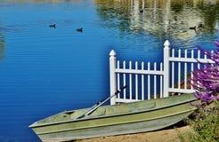 Een roeiboot op de kust van een meer. Stock Foto