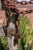 Een roestige ketting en een oud hangslot stock foto's