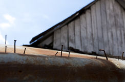 Een roestige spijker onder spijkers op het staal en het geroeste dakblad stock foto