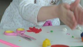 Een rolt de kleine meisjesspelen met plasticine, ballen met haar handen, zijn er cijfers en kleurpotloden op de Desktop stock footage
