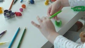 Een rolt de kleine meisjesspelen met plasticine, ballen, zijn er cijfers en kleurpotloden op de Desktop, de ontwikkeling stock videobeelden