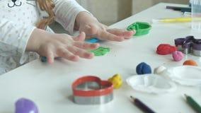Een rolt de kleine meisjesspelen met plasticine, ballen, zijn er cijfers en kleurpotloden op de Desktop, de ontwikkeling stock footage