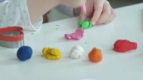 Een rolt de kleine meisjesspelen met plasticine, ballen, zijn er cijfers en kleurpotloden op de Desktop, de ontwikkeling stock video