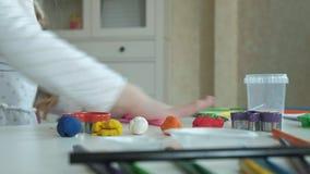 Een rolt de kleine meisjesspelen met plasticine, het met haar handen, zijn er cijfers en kleurrijke potloden op de Desktop, stock videobeelden