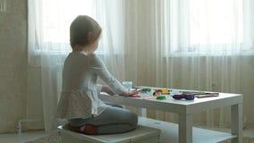 Een rolt de kleine meisjesspelen met plasticine, het met haar handen, zijn er cijfers en kleurrijke potloden op de Desktop, stock footage