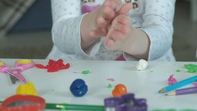 Een rolt de kleine meisjesspelen met plasticine, het met haar handen, zijn er cijfers en kleurrijke potloden op de Desktop, stock video