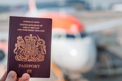 Een rood Brits die paspoort tegen een achtergrond van een generisch vliegtuig op een heldere zonnige dag wordt gesteund stock afbeelding