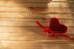 Een rood hart ligt op de houten lijst royalty-vrije stock afbeelding