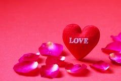 Een rood hart vormde met Liefde en nam bloemblaadjes op rode achtergrond toe Royalty-vrije Stock Foto