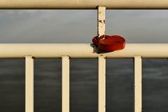Een rood metaalslot in de vorm van een hart hangt op een roestig wit rooster van een traliewerk van de rivierdijk royalty-vrije stock afbeeldingen