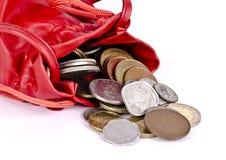 Een rood muntstuk, geldzak met muntstukken die uitgieten stock afbeeldingen
