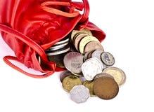 Een rood muntstuk, geldzak met muntstukken die uitgieten royalty-vrije stock afbeelding