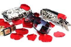 Een Rood nam bloemblaadjes, vrouwen` s toebehoren, zonnebril, horloge, portefeuille, sleutels in stilleven op een witte achtergro Stock Afbeelding