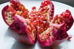 Een rood, rijp en sappig fruit van een ronde granaat ligt alleen op een ronde witte plaat Stock Foto