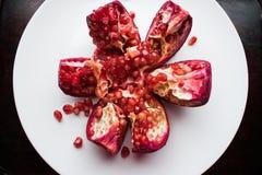 Een rood, rijp en sappig fruit van een ronde granaat ligt alleen op een ronde witte plaat Stock Fotografie