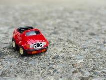 Een rood stuk speelgoed parkeerterrein op ruwe cementweg Stock Fotografie